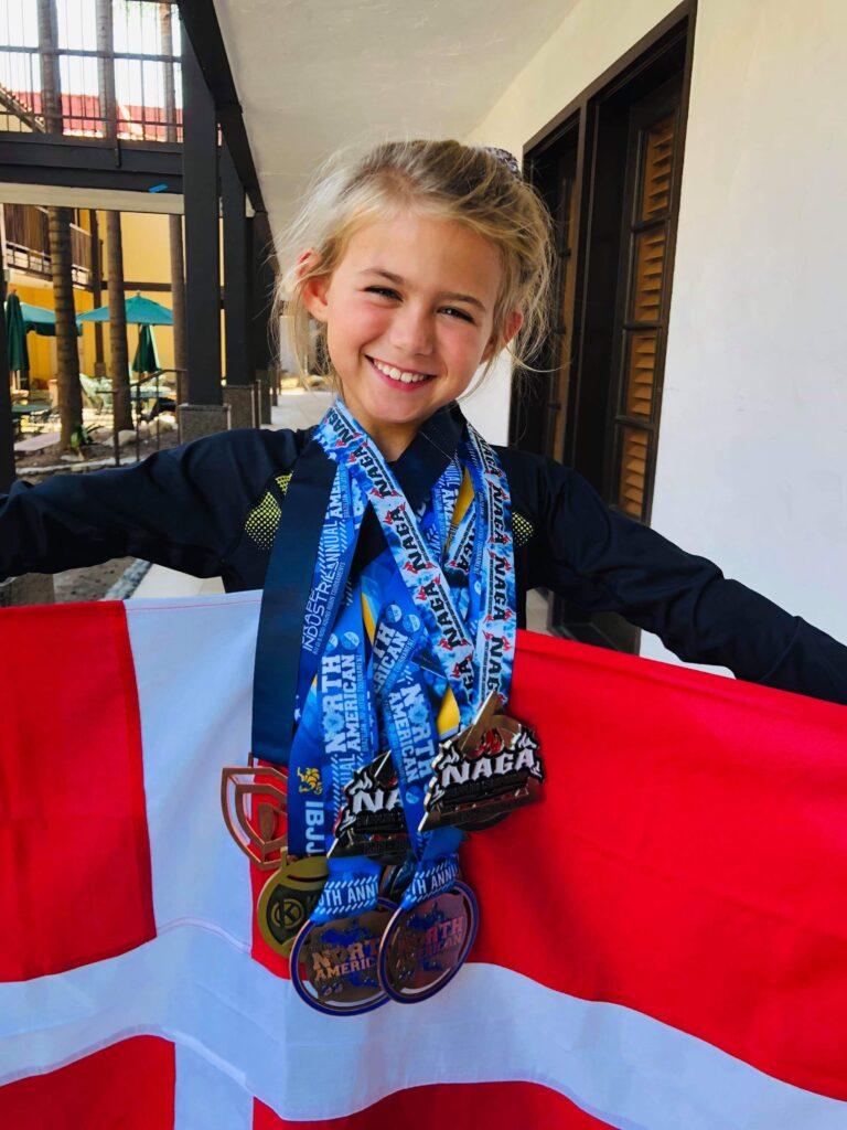 Her står Evolete Elise Boris med alle sine USA TOUR Medaljer samt Danmarks flag